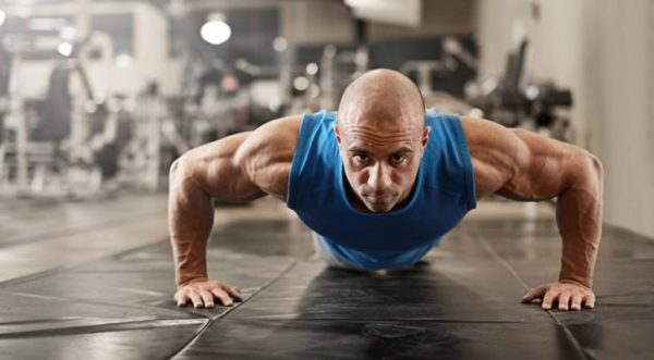 52845999 - active and muscular man keeping fit by doing pushups on a floor mat - filtered image